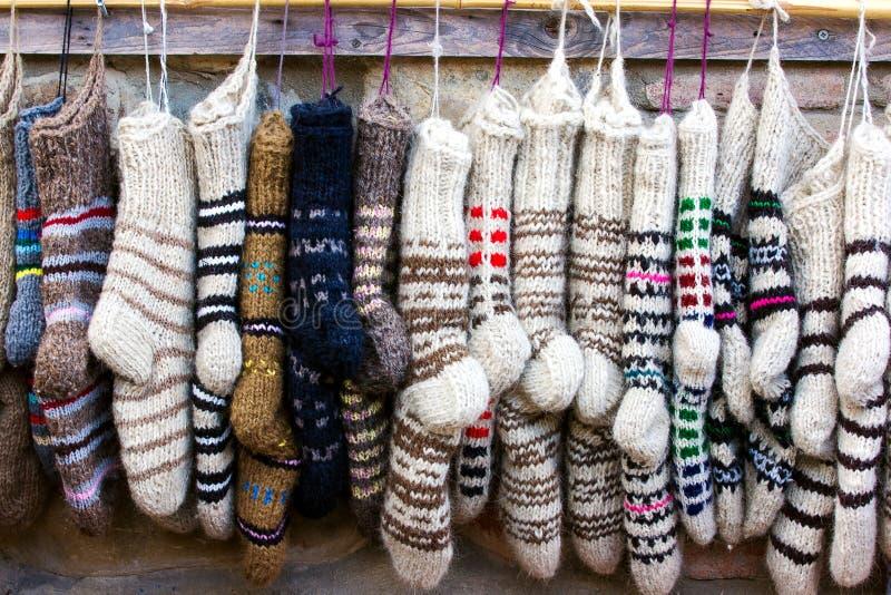 Νέες πλεκτές κάλτσες μαλλιού των διαφορετικών χρωμάτων και των διακοσμήσεων που κρεμούν σε μια σειρά στοκ φωτογραφία