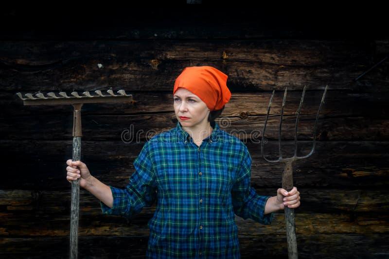 Νέες στάσεις γυναικών με ένα pitchfork κοντά σε έναν σταύλο σε ένα αγρόκτημα στοκ φωτογραφίες με δικαίωμα ελεύθερης χρήσης