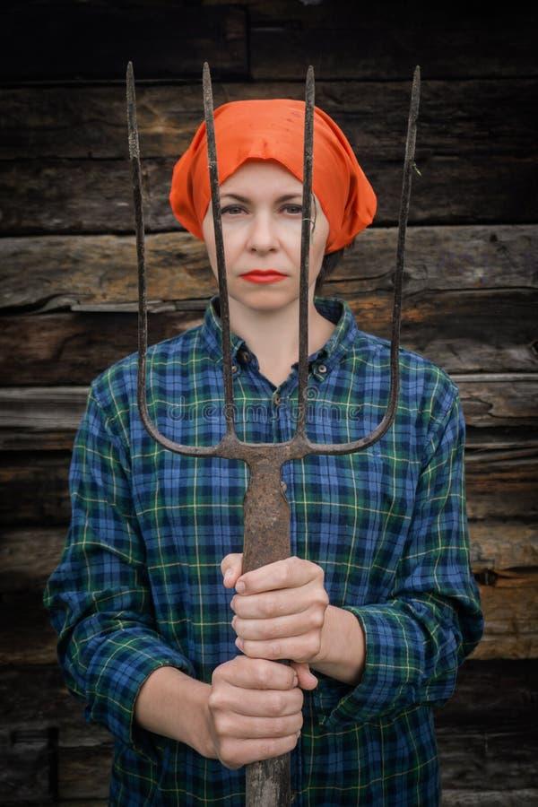 Νέες στάσεις γυναικών με ένα pitchfork κοντά σε έναν σταύλο σε ένα αγρόκτημα στοκ εικόνα με δικαίωμα ελεύθερης χρήσης