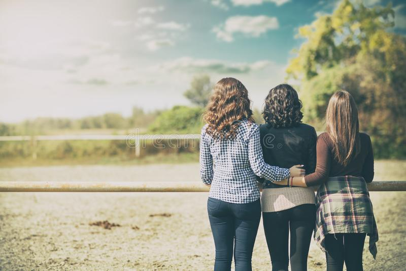 νέες τρεις κυρίες που στέκονται πέρα από το υπόβαθρο φύσης ομορφιάς στοκ εικόνα