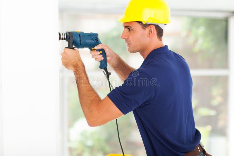 Τρυπώντας με τρυπάνι τοίχος οικοδόμων στοκ φωτογραφία