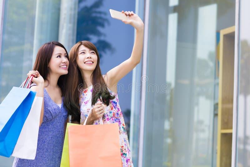 Νέες τσάντες αγορών εκμετάλλευσης γυναικών που παίρνουν τις φωτογραφίες στοκ εικόνες