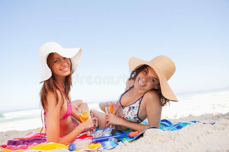 Νέες χαμογελώντας γυναίκες που βρίσκονται στις πετσέτες παραλιών στοκ φωτογραφία