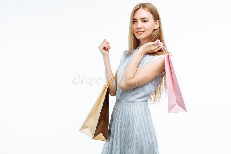 Νέες όμορφες αγορές κοριτσιών, που θέτουν με τις τσάντες δώρων, στο άσπρο β στοκ φωτογραφίες