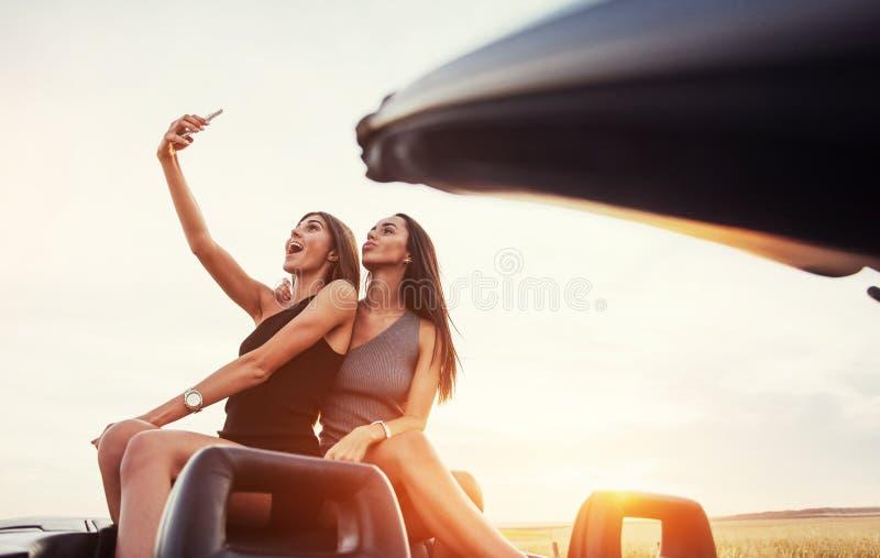 Νέες δύο γυναίκες σε έναν βλαστό φωτογραφιών Κορίτσια που θέτουν πρόθυμα στοκ εικόνα