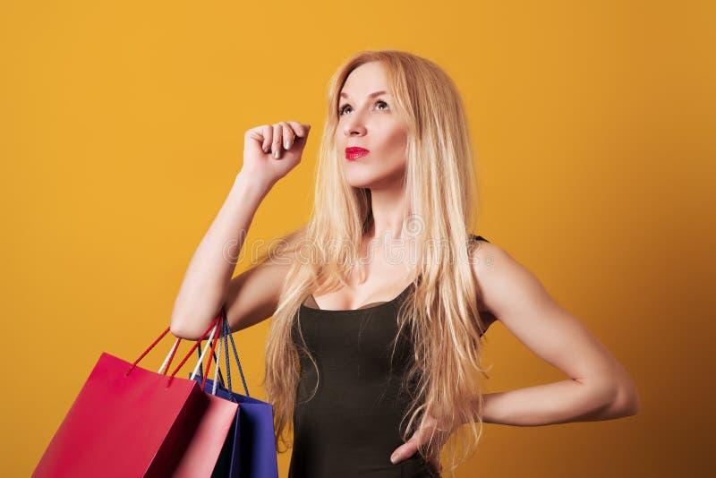 Νέες blondy τσάντες αγορών εκμετάλλευσης κοριτσιών που απομονώνονται πέρα από το κίτρινο υπόβαθρο στοκ εικόνες με δικαίωμα ελεύθερης χρήσης