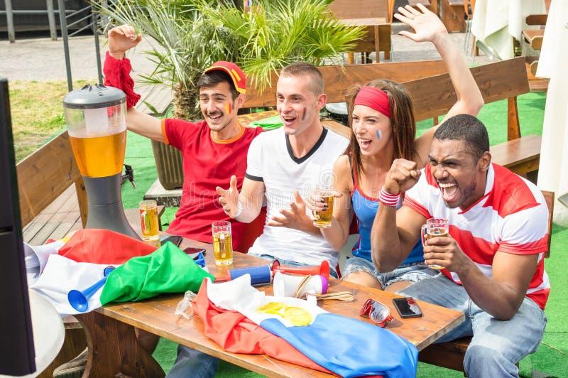 Νέοι ανεμιστήρες οπαδών ποδοσφαίρου ενθαρρυντικοί με τον αθλητισμό προσοχής μπύρας στοκ φωτογραφίες