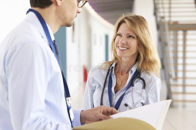 Νέοι αρσενικοί και θηλυκοί γιατροί που συσκέπτονται ο ένας με τον άλλον στοκ εικόνες με δικαίωμα ελεύθερης χρήσης