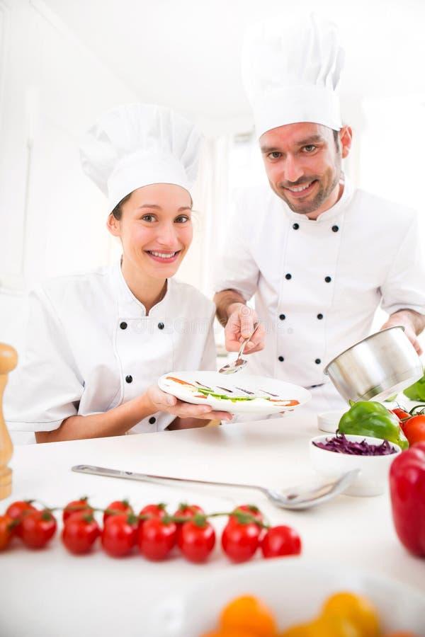 Νέοι αρχιμάγειρες επαγγελματιών attractives που μαγειρεύουν από κοινού στοκ εικόνα με δικαίωμα ελεύθερης χρήσης