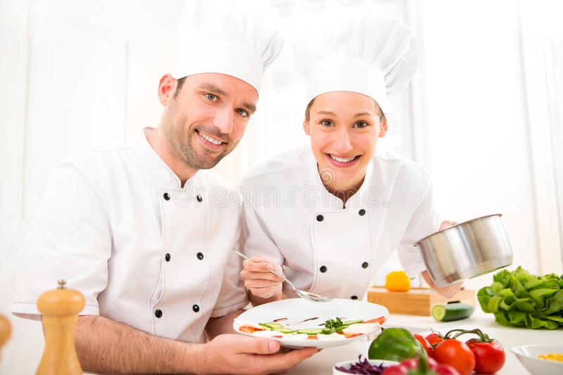 Νέοι αρχιμάγειρες επαγγελματιών attractives που μαγειρεύουν από κοινού στοκ φωτογραφίες