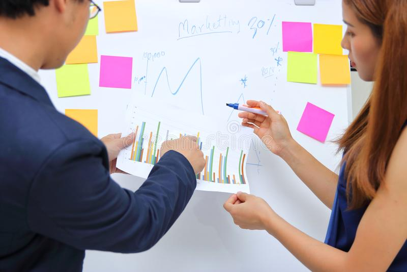 Νέοι βέβαιοι επιχειρησιακοί συνάδελφοι που αναλύουν τα έγγραφα και εργασία μαζί στην αρχή στοκ φωτογραφία