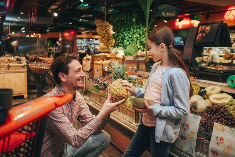 Νέοι γονέας και κόρη στο μανάβικο Ο ευτυχής πατέρας δίνει τον ανανά παιδιών Εξετάζει το γονέα και το χαμόγελο Κρατά στοκ φωτογραφία