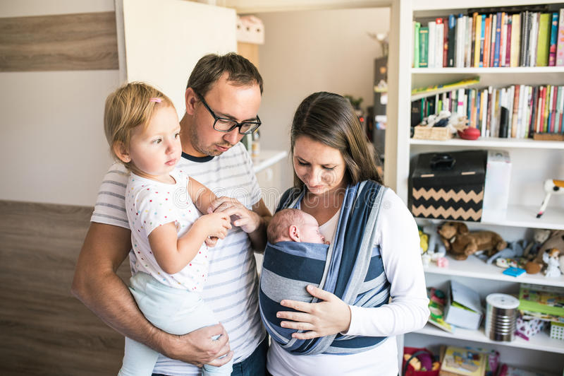 Νέοι γονείς με τα παιδιά στο φορέα σφεντονών και μωρών στοκ εικόνα με δικαίωμα ελεύθερης χρήσης