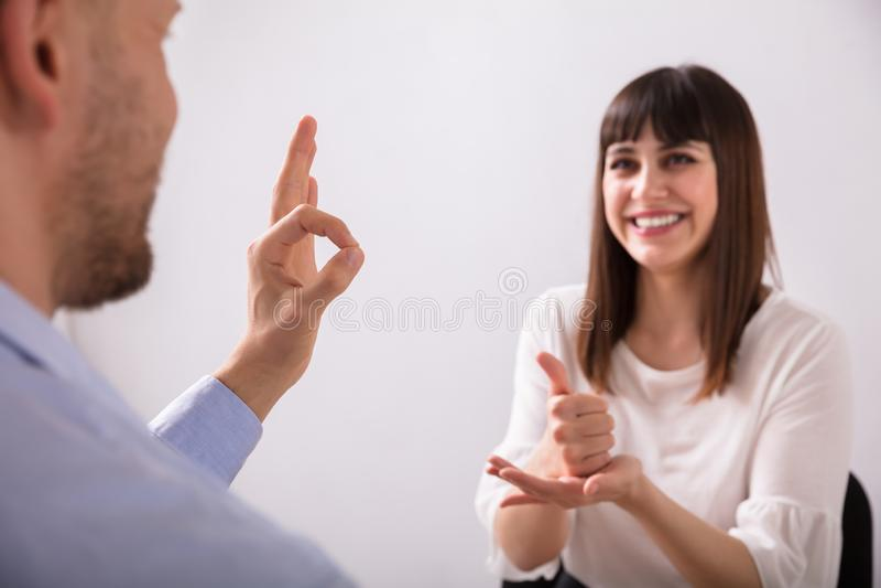 Νέοι γυναίκα και άνδρας που μιλούν με τη γλώσσα σημαδιών στοκ φωτογραφίες με δικαίωμα ελεύθερης χρήσης