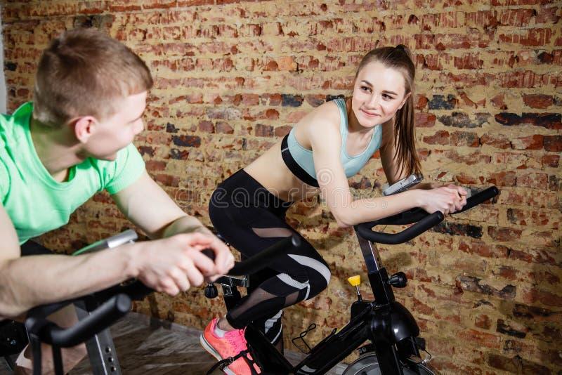 Νέοι γυναίκα και άνδρας που φορούν την κατάρτιση στην ανακύκλωση των μηχανών στην ελαφριά ευρύχωρη γυμναστική στοκ φωτογραφία με δικαίωμα ελεύθερης χρήσης