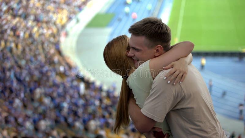 Νέοι γυναίκα και τύπος που αγκαλιάζουν κατά τη διάρκεια του αγώνα ποδοσφαίρου την αγαπημένη νίκη ομάδων ποδοσφαίρου στοκ εικόνα