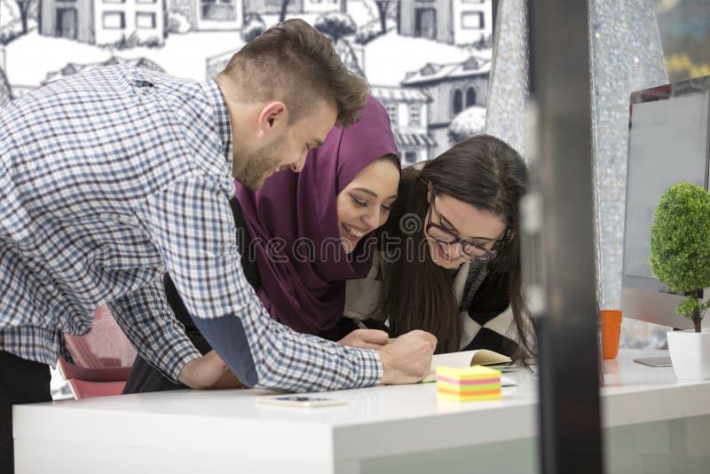Νέοι δημιουργικοί επιχειρηματίες ξεκινήματος στη συνεδρίαση στο σύγχρονο γραφείο που κάνει τα σχέδια και τα προγράμματα στοκ εικόνα