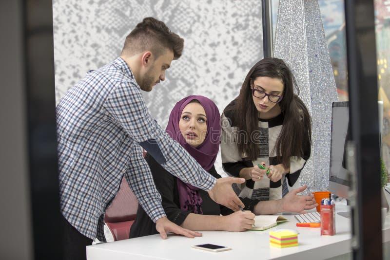 Νέοι δημιουργικοί επιχειρηματίες ξεκινήματος στη συνεδρίαση στο σύγχρονο γραφείο που κάνει τα σχέδια και τα προγράμματα στοκ φωτογραφία