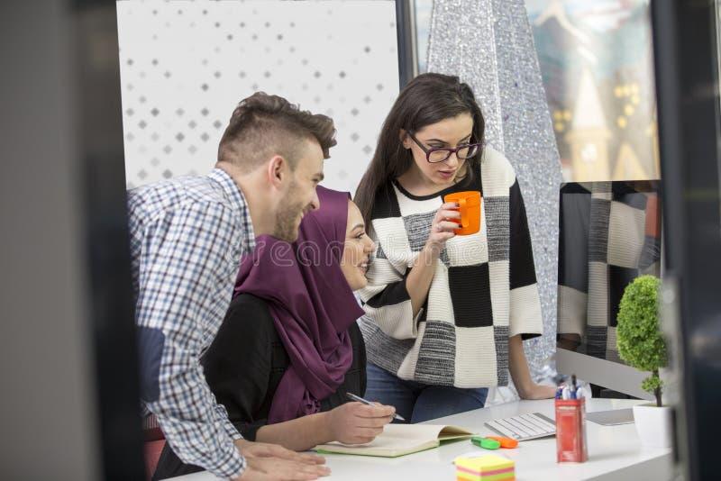 Νέοι δημιουργικοί επιχειρηματίες ξεκινήματος στη συνεδρίαση στο σύγχρονο γραφείο που κάνει τα σχέδια και τα προγράμματα στοκ εικόνες