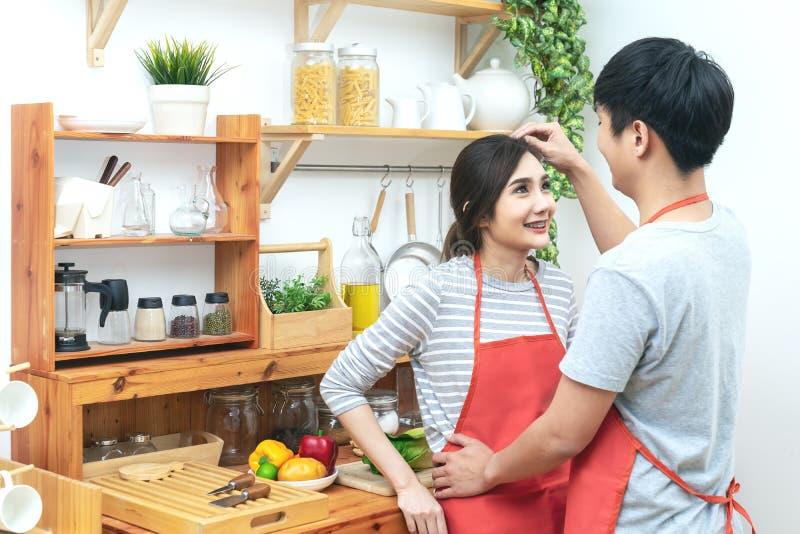 Νέοι ελκυστικοί ασιατικοί άνδρας και γυναίκα ζευγών που εξετάζουν η μια την άλλη στην κουζίνα Νέος παντρεμένος ασιατικός τρόπος ζ στοκ φωτογραφία με δικαίωμα ελεύθερης χρήσης
