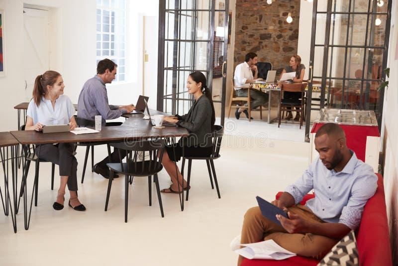Νέοι επαγγελματίες που εργάζονται σε ένα ανοικτό γραφείο σχεδίων στοκ εικόνα