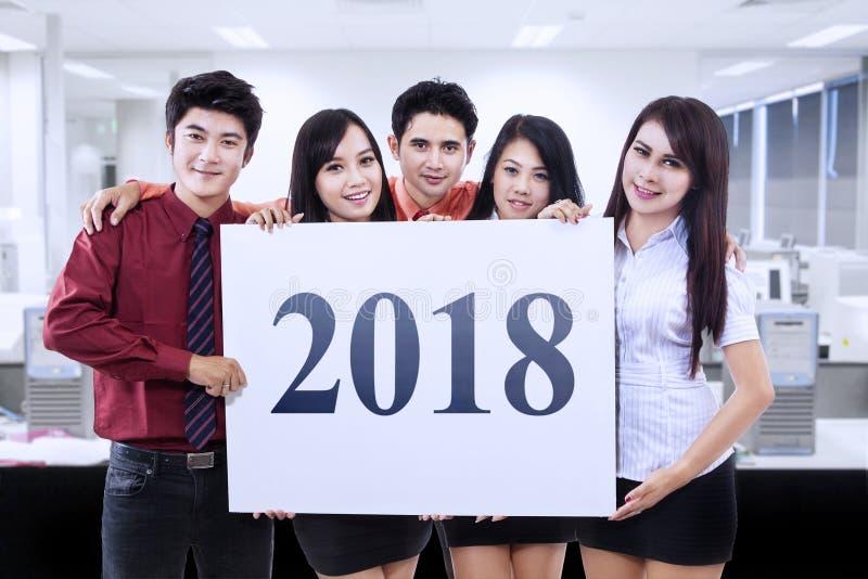 Νέοι επιχειρηματίες που παρουσιάζουν αριθμούς 2018 στοκ φωτογραφία