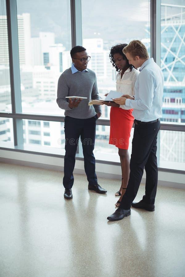 Νέοι επιχειρηματίες που συζητούν από τα παράθυρα γυαλιού στοκ φωτογραφίες