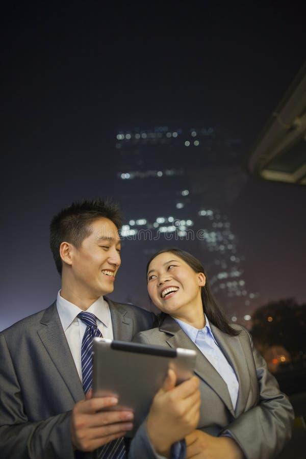 Νέοι επιχειρηματίες που χαμογελούν και που κρατούν την ψηφιακή ταμπλέτα, νύχτα και υπαίθρια στοκ φωτογραφία με δικαίωμα ελεύθερης χρήσης