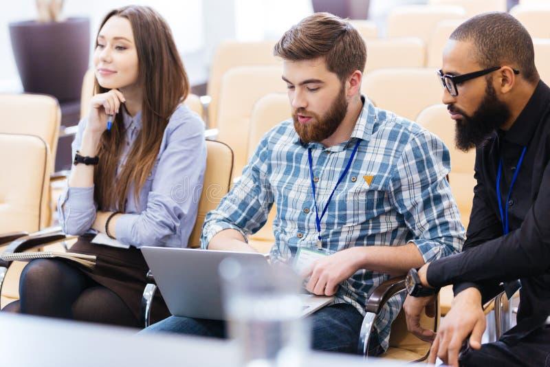 Νέοι επιχειρηματίες που χρησιμοποιούν τη συνεδρίαση lap-top στη συνεδρίαση στοκ εικόνα με δικαίωμα ελεύθερης χρήσης