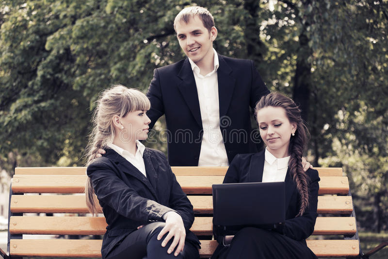 Νέοι επιχειρηματίες που χρησιμοποιούν το lap-top σε ένα πάρκο πόλεων στοκ φωτογραφία