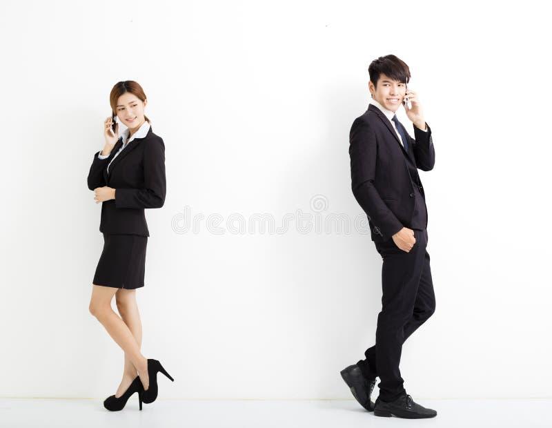 Νέοι επιχειρησιακοί άνδρας και γυναίκα που μιλούν στο τηλέφωνο στοκ εικόνα με δικαίωμα ελεύθερης χρήσης
