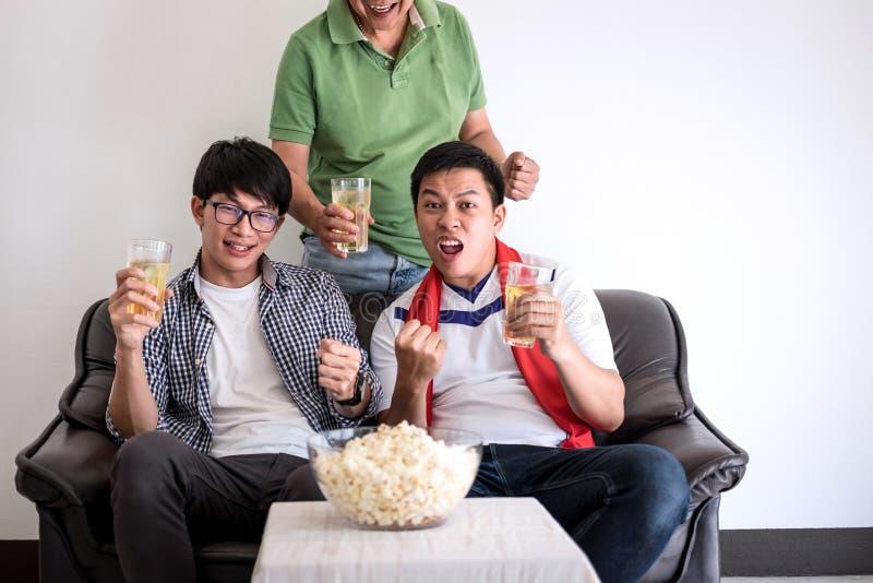 Νέοι ευτυχείς ασιατικοί οικογένεια ή οπαδοί ποδοσφαίρου ατόμων που προσέχει το ποδόσφαιρο μΑ στοκ εικόνες
