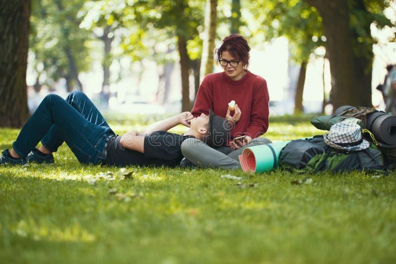 Νέοι ευτυχείς οδοιπόροι ζευγών που καταψύχουν έξω στο θερινό πάρκο στοκ εικόνα