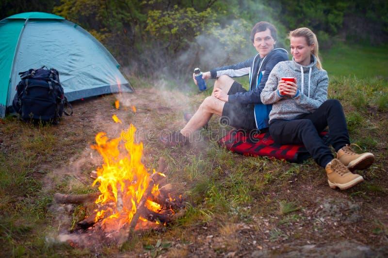 Νέοι ευτυχείς ταξιδιώτες ζευγών που στο δασικό χαμογελώντας ζεύγος σχετικά με στοκ εικόνες