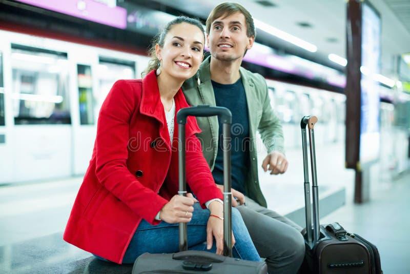 Νέοι θετικοί εύθυμοι επιβάτες με τις αποσκευές που περιμένουν το trai στοκ φωτογραφία με δικαίωμα ελεύθερης χρήσης