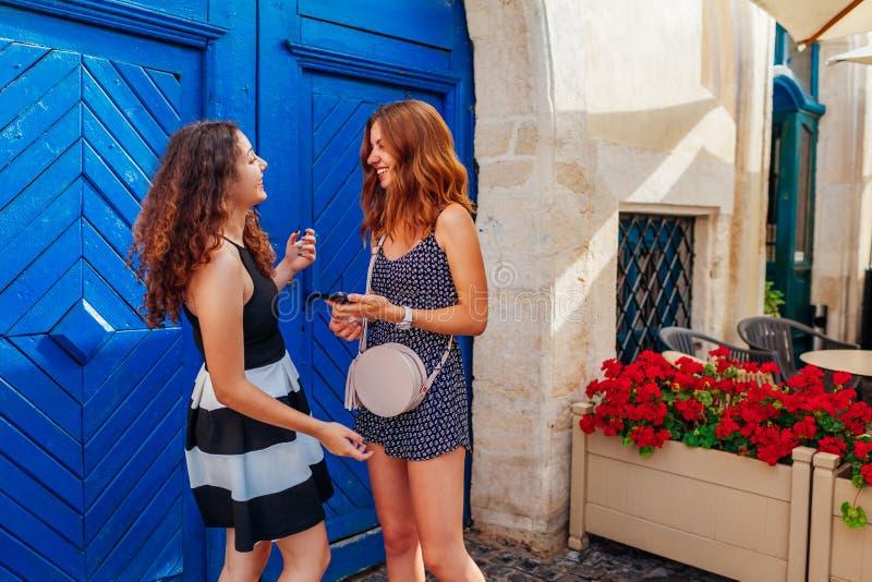 Νέοι θηλυκοί φίλοι που μιλούν χρησιμοποιώντας το smartphone από τον καφέ Ευτυχείς όμορφες γυναίκες που γελούν και που έχουν τη δι στοκ φωτογραφίες