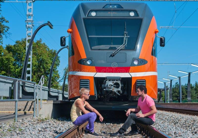 Νέοι καθιερώνοντες τη μόδα τύποι μπροστά από το τραίνο στοκ φωτογραφία με δικαίωμα ελεύθερης χρήσης