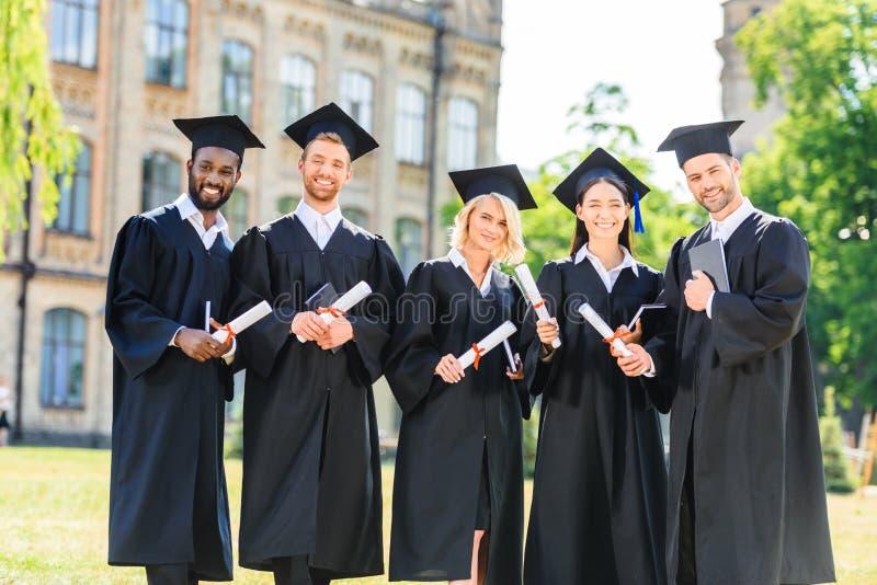 νέοι κλιμακωτοί σπουδαστές στα ακρωτήρια που κρατούν τα διπλώματα και το κοίταγμα στοκ εικόνες