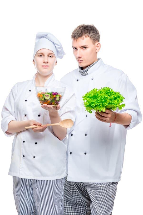 νέοι μάγειρες στα κοστούμια με τη σαλάτα στα χέρια στοκ εικόνα με δικαίωμα ελεύθερης χρήσης