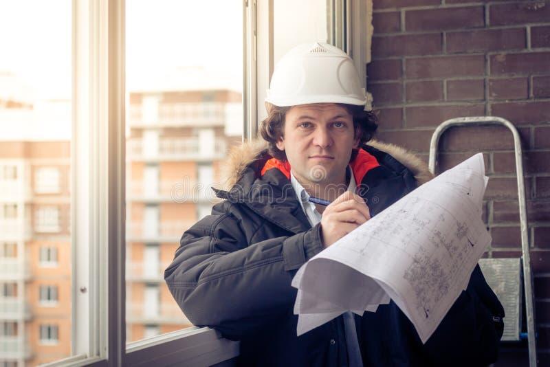 Νέοι μηχανικοί που χρησιμοποιούν το σημείο μανδρών στο έγγραφο σχεδιαγραμμάτων για να εξετάσει τη δομή του σπιτιού πρίν παρουσιάζ στοκ εικόνες