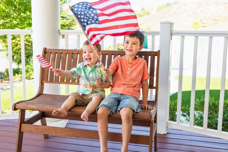 Νέοι μικτοί κινεζικοί καυκάσιοι αδελφοί φυλών που παίζουν με τις αμερικανικές σημαίες στοκ εικόνες