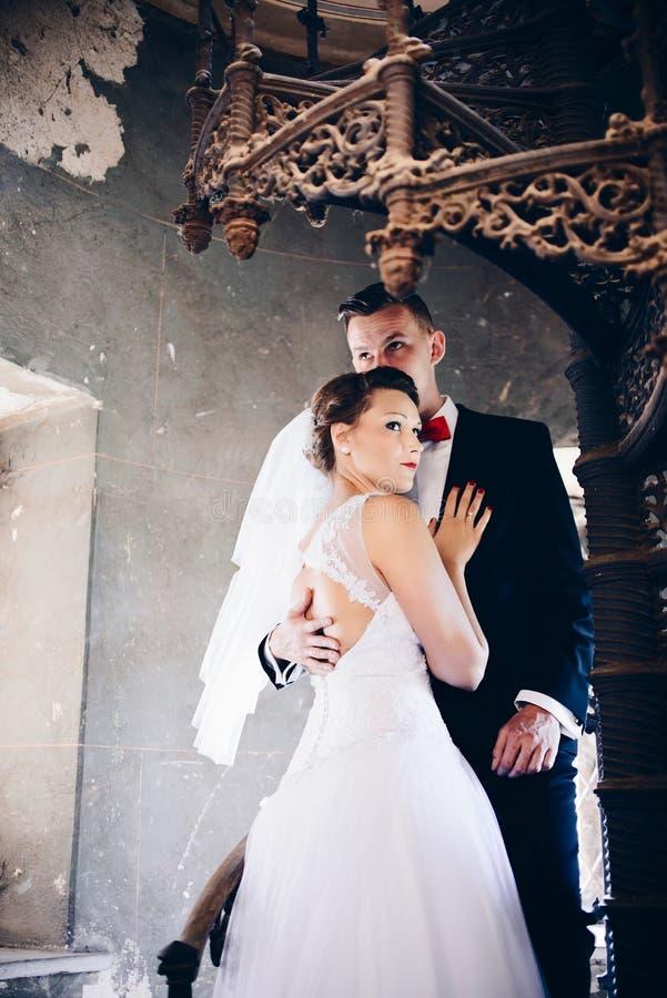 Νέοι νύφη και νεόνυμφος στα παλαιά σκαλοπάτια ευτυχής εκλεκτής ποιότητας γάμος ημέρας ζευγών ιματισμού Γαμήλια σύνοδος στοκ εικόνες