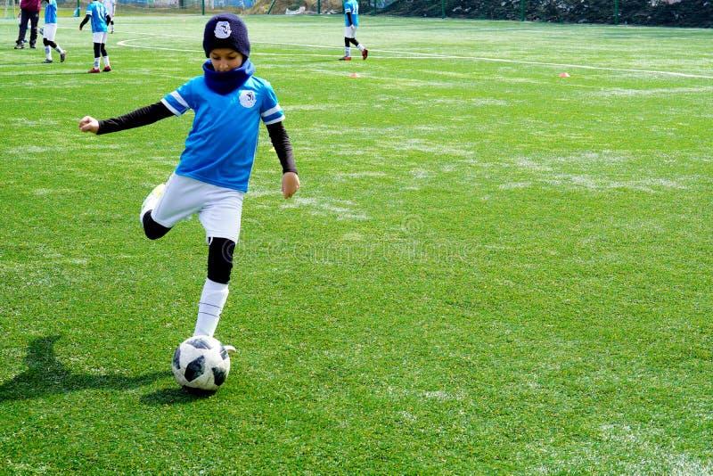 Νέοι ποδοσφαιριστές που τρέχουν μετά από τη σφαίρα Ομάδα ποδοσφαίρου παιδιών στην πίσσα Έδαφος κατάρτισης ποδοσφαίρου παιδιών στοκ εικόνες