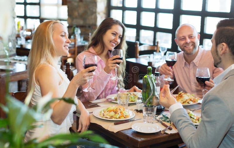 Νέοι που απολαμβάνουν τα τρόφιμα στην ταβέρνα στοκ εικόνα με δικαίωμα ελεύθερης χρήσης