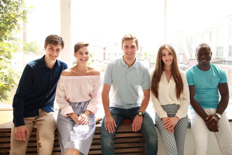Νέοι που εξετάζουν τη κάμερα με το χαμόγελο καθμένος στο γραφείο στοκ εικόνες