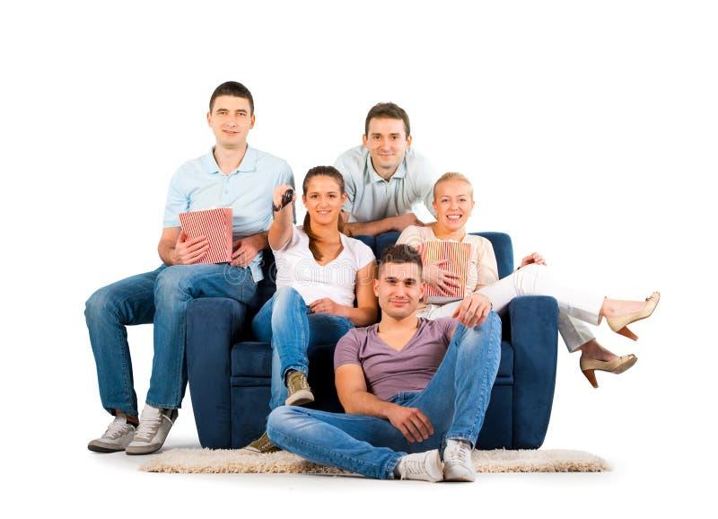 Νέοι που κάθονται σε έναν καναπέ με τον τηλεχειρισμό, χαμόγελο στοκ εικόνες
