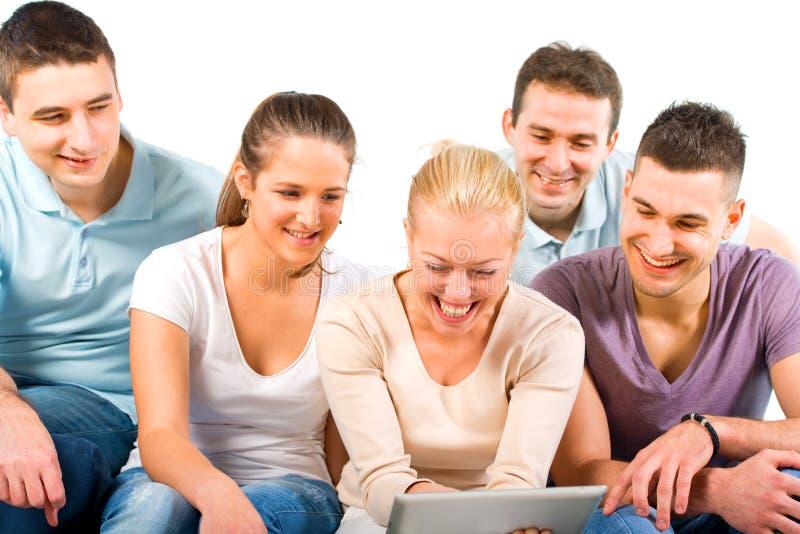 Νέοι που κάθονται σε έναν καναπέ, που εξετάζει μια ταμπλέτα στοκ εικόνα