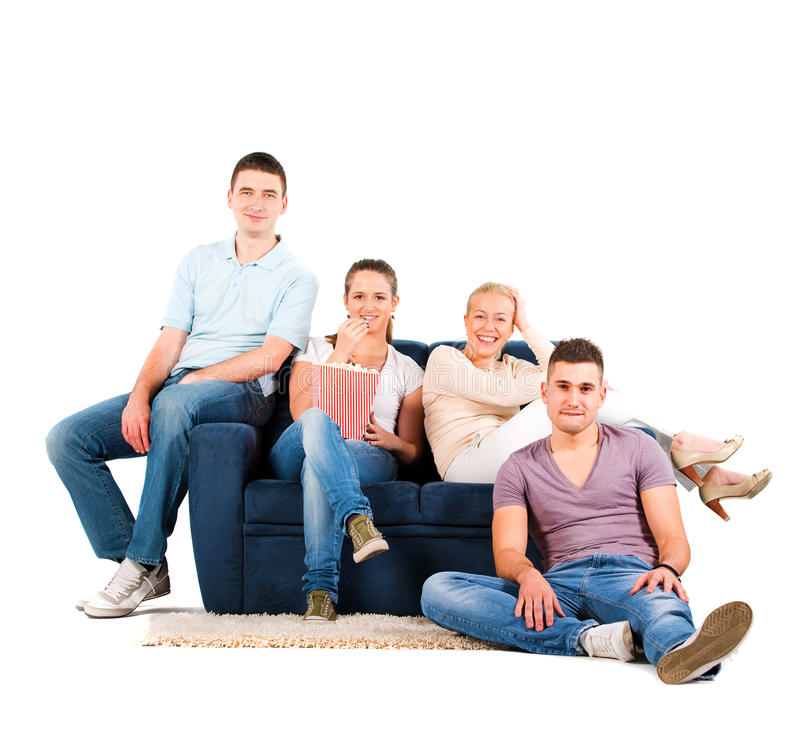 Νέοι που κάθονται σε ένα χαμόγελο καναπέδων στοκ εικόνες