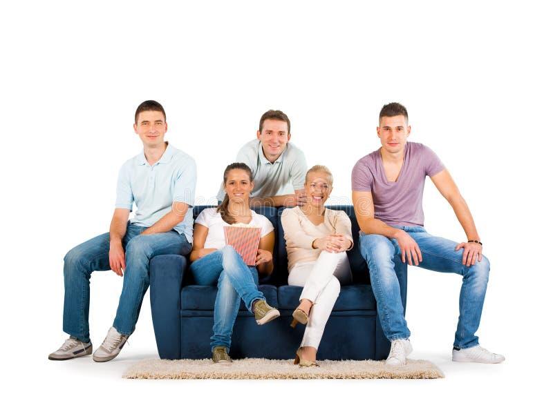 Νέοι που κάθονται σε ένα χαμόγελο καναπέδων στοκ εικόνες με δικαίωμα ελεύθερης χρήσης