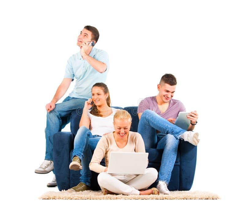 Νέοι που κάθονται στον καναπέ με τις συσκευές τους στοκ εικόνες